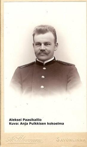 Seepiansävyinen visiittikorttikuva (ylävartalokuva) virkapukuisesta postiljooni Aleksei Paasikalliosta ilman hattua.