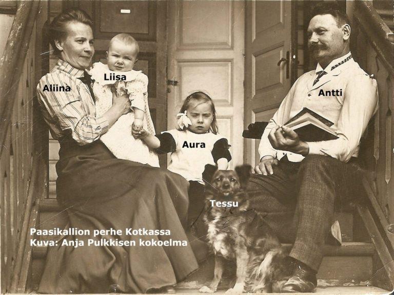 Mustavalkovalokuva, missä Aliina ja Antti Paasikallio istuvat ulkorappusilla lapsiensa Liisan ja Auran sekä Tessu-koiran kanssa Kotkassa.