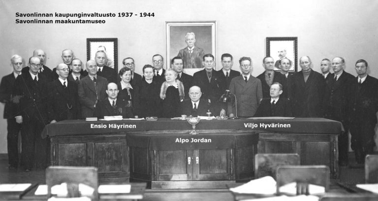 Mustavalkovalokuva vuosina 1937–1944 toimineesta kaupunginvaltuustosta. Ensio Häyrinen, Alpo Jordan ja Viljo Hyvärinen istuvat pöydänääressä ja muut seisovat heidän takanaan.