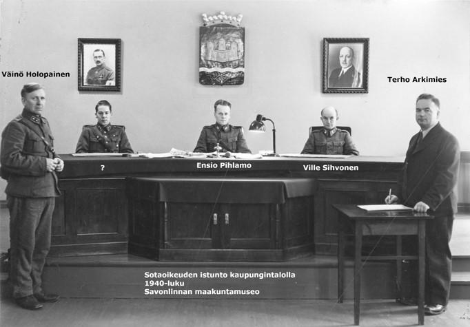 Mustavalkovalokuva kaupungintalon sotaoikeuden istunnosta 1940-luvulla, seisomassa Väinö Holopainen ja Terho Arkimies, istumassa Ensio Pihlamo, Ville Sihvonen sekä yksi tunnistamaton mies. Muut ovat sotilasasuissa paitsi Arkimies.