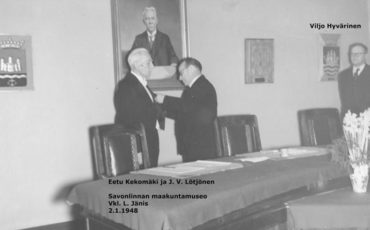Mustavalkovalokuva, jossa kaupunginvaltuuston uusi puheenjohtaja J. V. Lötjönen kiinnittää jotain väistyvän puheenjohtajan Eetu Kekomäen rintapieleen – Viljo Hyvärinen seuraa sivusta.