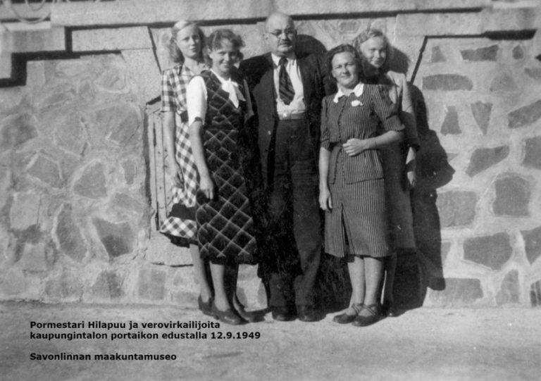 Mustavalkovalokuvassa pormestari Hilapuu ja verotoimiston neljä naistyöntekijää tiivissä ryhmäkuvassa syksyllä 1949 kaupungintalon edessä.