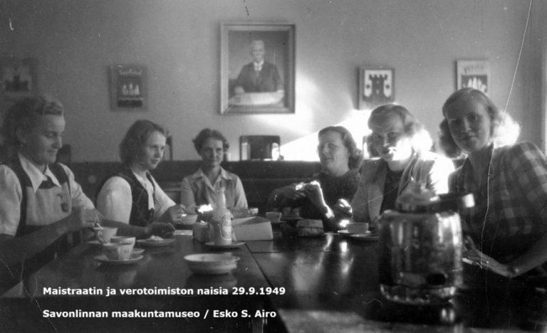 Mustavalkovalokuvassa kuusi naista on kokoontunut juomaan kahvia valtuustosalissa.