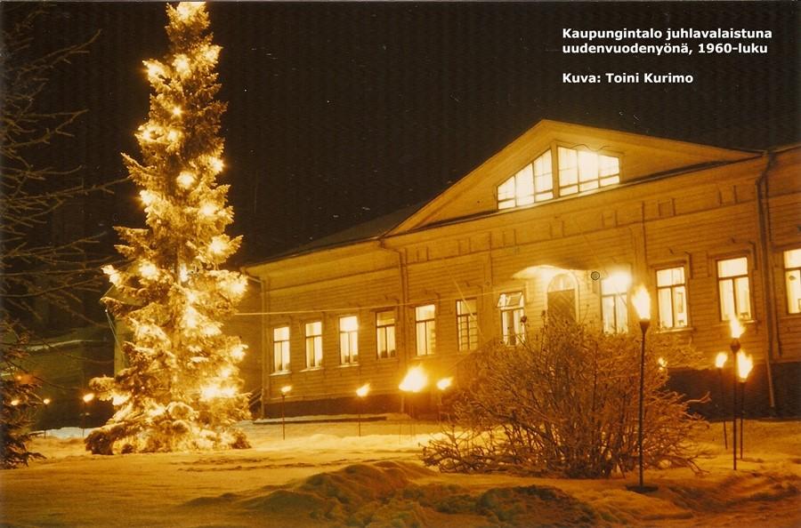 Värivalokuva juhlavalaistusta kaupungintalosta uudenvuodenyönä 1960-luvulla. Kaupungintalon edustan kuusessa on jouluvalot, ja pitkävartiset soihdut palavat talon edustan auratun kadun vieressä.
