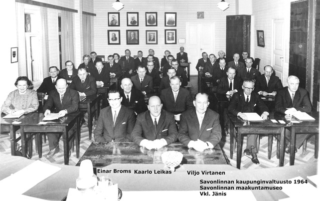 Mustavalkovalokuva kuvattuna puheenjohtajan pöydältä valtuustosalin takaosaan päin. Ahdasta on, kun Einar Bromsin, Kaarlo Leikkaan ja Viljo Virtasen lisäksi salissa on lisäksi 34 valtuuston jäsentä.