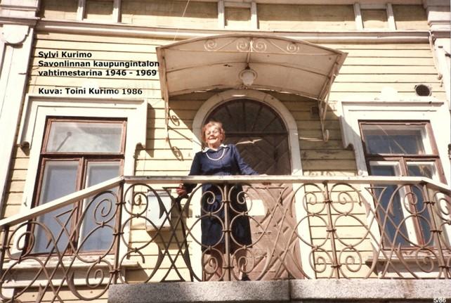 Värivalokuvassa kaupungintalossa vahtimestarina vuosina 1946–1969 työskennellyt Sylvi Kurimo pääsisäänkäynnin portaikon ylätasanteella metallikaiteen ääressä.