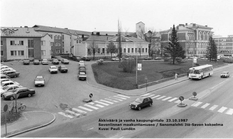 Mustavalkovalokuva vanhasta kaupungintalosta ja sen uudisosasta eli äkkiväärästä lokakuussa 1987 Olavinkadun toiselta puolelta kuvattuna. Äkkiväärän edusta on täynnä henkilöautoja, ja bussi on seisahtunut vanhan kaupungintalon eteen pysäkille.