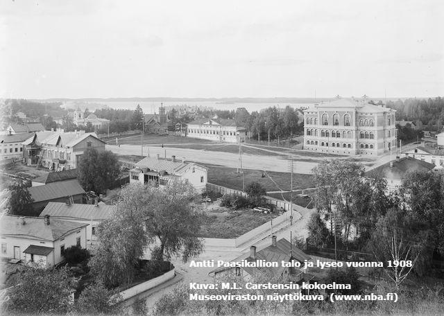 Mustavalkovalokuva Antti Paasikallion talosta lyseon vierellä vuonna 1908.