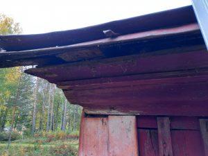 Punaiseksi maalatun saumapeltikaton kulmaraudoilla tuettu jalkakouru on painunut matalaksi.