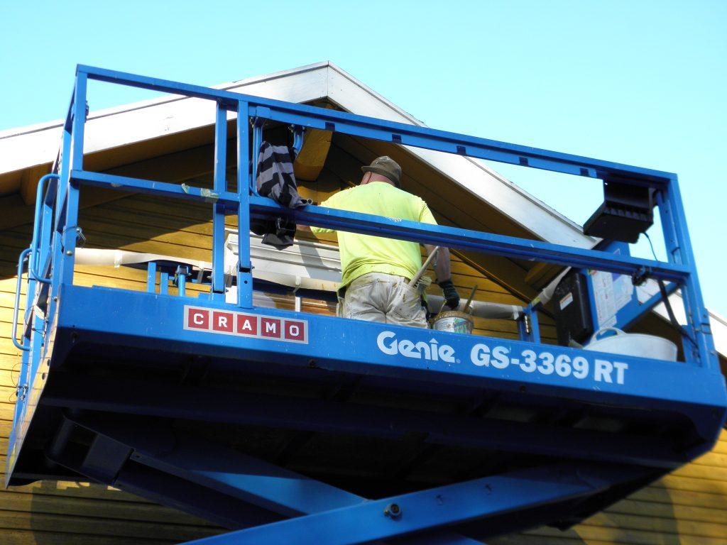 Työmies pensselimaalaa saksinostimella kalastajatilan päärakennuksen päätykolmiota keltaisella petrooliöljymaalilla.