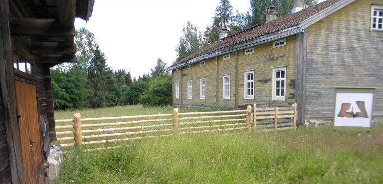 Maalaamattoman tallin ja keltaiseksi maalatun, mutta haalistuneen asuinrakennuksen yhdistää paksuista tolpista ja vaakariu'uista pystytetty aita, jonka molemmin puolin kasvaa korkeaa heinää.