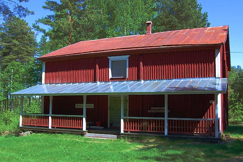 Haukivuoren kotiseutumuseon punaiseksi maalattu viljamakasiini, jonka avokuisti on uusittu, ja saumapeltikatto kiiltää auringon valossa.