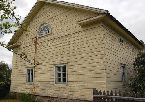 Kuvassa Lyytikkälän tilan päärakennuksen vaakavuorattua ja vaaleaksi maalattua päätyä ruutuikkunoineen. Päätykolmiossa sijaitsevat kissanpenkit ja hämähäkkiverkkoa muistuttava lunetti-ikkuna.