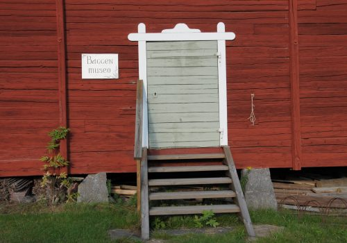 Baggen museon sisäänkäynti eli puuportaat nousevat harmaanvihreälle makasiinin ovelle, joka vuorilaudat on maalattu valkeiksi. Hirsiseinä on punamullattu, ja perustuksen ovat välikivet lohkokivistä.