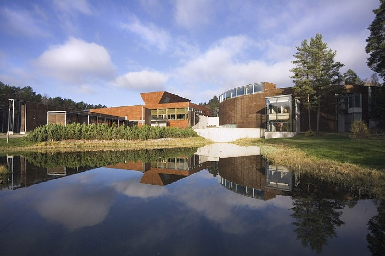 Luston näyttely rakennus kuvastuu peilityynen lammen pintaan kesällä.