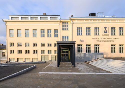 Ulkokuva entisestä koulurakennuksesta eli nykyisestä Sodan ja rauhan keskus Muistista: vaaleankeltaiseksi maalatut seinät ja uusi kirkas saumapeltikatto.
