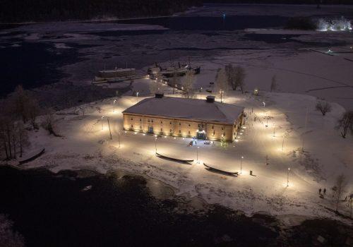 Linnan tornista otettu talvikuva Riihisaaresta: lunta maassa ja museorakennus valaistuna.