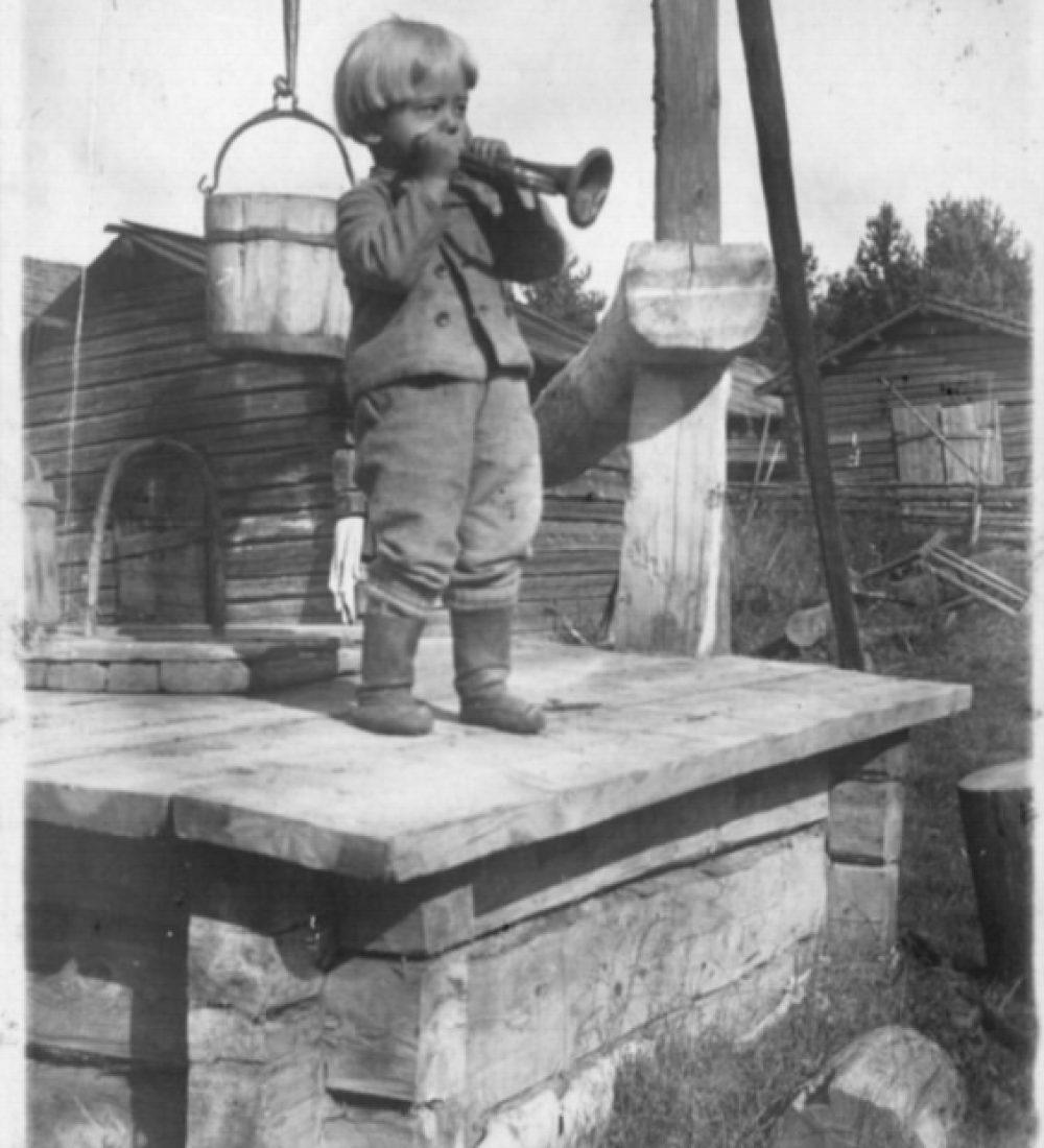 Pieni poika soittamassa torvea vinttikaivon kannella maalaistalon pihassa. Taustalla hirsisiä piharakennuksia. Savonlinnan maakuntamuseo.