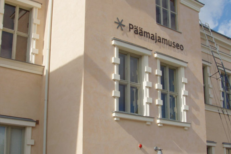 Päämajamuseon sisäänkäynti kuvattuna ulkoapäin: vaaleanpunertavat, hienoksirapatut seinät ja valkoisen lista.