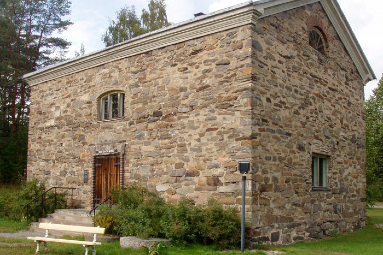 Ulkokuva kivistä muuratusta Suur-Savo museosta, jonka etusivulla kasvaa pensaita.