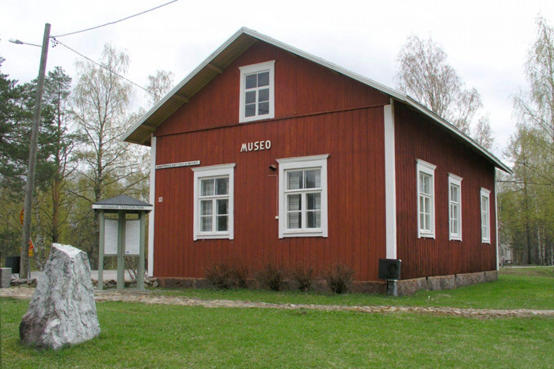 Pystyvuorattu, punainen ja otsa- ja räystäs- ja pielilaudoiltaan valkeaksi maalattu vanha kunnastalo, jossa on satulakatto ja kuusiruutuiset ikkunat.