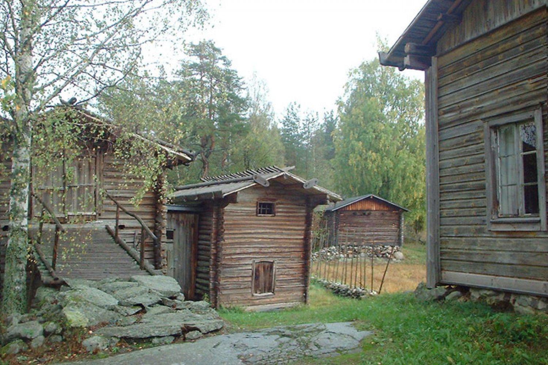 Näkymä pihasta saunalle. Oikealla päärakennuksen nurkkaa, keskellä talli ja putka-aitta ja kauimpana sauna. Kaikki maalaamattomia ja vuoraamattomia pitkänurkkaisia hirsirakennuksia.
