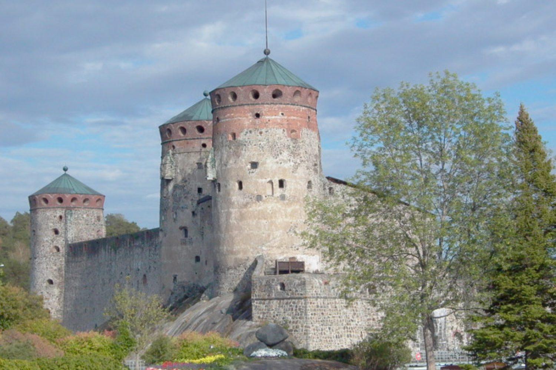 Olavinlinna kuvattuna Tallisaarelta, kolme tornia näkyvissä.