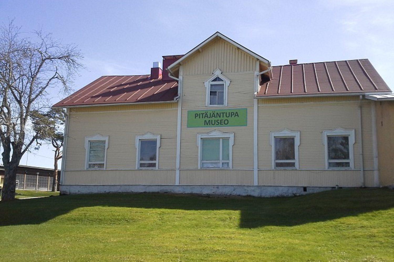Ulkokuva Pitäjäntupamuseosta eli vaaka- ja pystyvuoratusta rakennuksesta, joka on maalattu keltaiseksi.