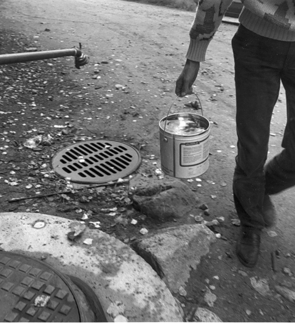 Savonlinna, Lähteelän vedenottamon kaivo. Mies kantaa peltipurkilla ja muovisangolla vettä. Savonlinnan maakuntamuseo, sanomalehti Itä-Savon kuva-arkisto, kuvaaja Pauli Lundén, 7.9.1990.